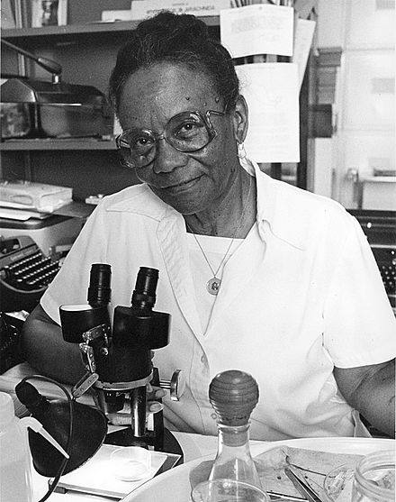 An African American woman sitting in a white lab coat in front a microscope